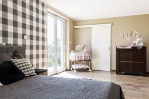 Beige bedroom with a newborn's corner